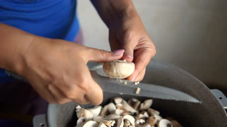 manjericão : Young woman cutting mushrooms in the kitchen Stock Footage
