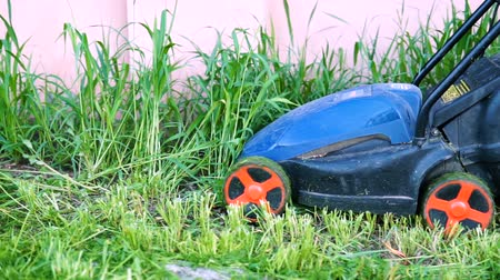 geri yaktı : Worker mowing a grass with lawn mower