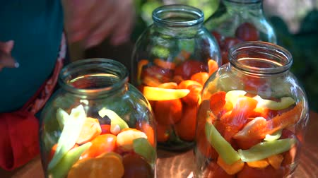 savanyúság : woman puts tomatoes in jar for preservation, preparation of canned vegetables