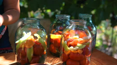 megőriz : woman puts tomatoes in jar for preservation, preparation of canned vegetables