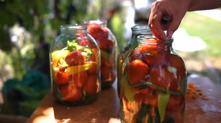 соленья : woman puts tomatoes in jar for preservation, preparation of canned vegetables