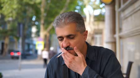 прораб : Adult man talking to camera and smoking sigarette.