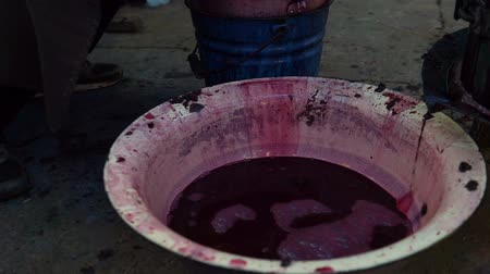 vinné sklepy : farmer working on fermentation of homemade wine. Pour the wine into the bucket. Moldova republic.