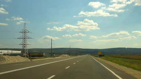 седан : The car is driving along the highway. Asphalt road between agricultural fields and driving cars. Front view. Стоковые видеозаписи