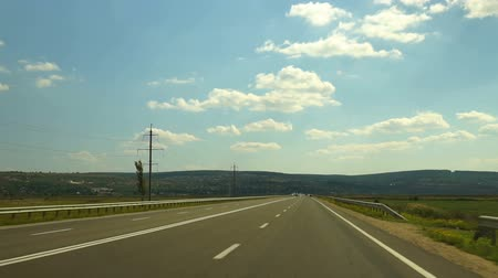 The car is driving along the highway. Asphalt road between agricultural fields and driving cars. Front view. Dostupné videozáznamy