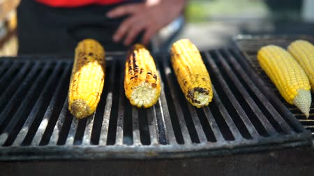 kukoricacső : Close up of appetizing grilled sweet corn on the bbq grill. Street food festival. Shef turn the corn on grill