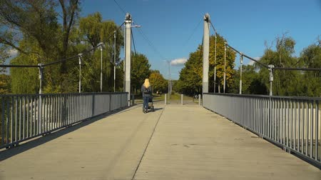 the suspension bridge : Camera walks across a bridge, behind a lady with a trolley. Steadicam shot.