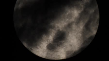 telescopic : Telescopic view on the full moon with the lunar surface details (marina, mountains, craters) visible. Clouds cover the Moon surface and move. The atmospheric turbulence and natural motion of the Moon due to the Earth rotation impart a realism to the video Stock Footage