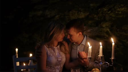 família : A couple on a romantic date, sitting at a beautifully laid table in the evening outdoors. Candlelight dinner