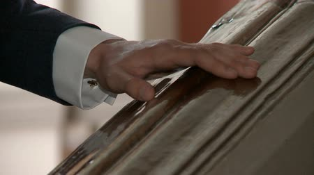 eleganckie : A man in a suit and a white shirt goes down the stairs, close-up the hand slides on the railing