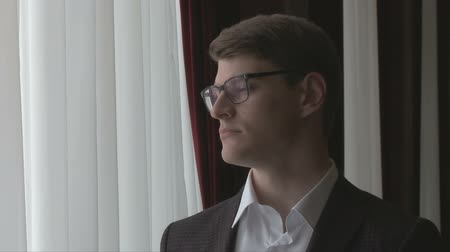 motivo : Young man, businessman wearing glasses, standing by the big window Stock Footage