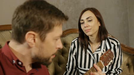 serenade : A young man plays the guitar for his lover indoors sitting on the couch Stock Footage