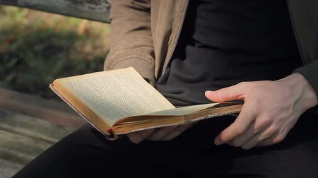 bookshop : A young man is reading an old ancient book in a park on a bench on a sunny day Stock Footage