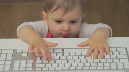 лечит : A small child of 1 year approaches the computer keyboard and heals the keys Стоковые видеозаписи