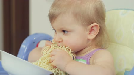 nepořádek : Charming little girl eating spaghetti with her fingers and enjoying it
