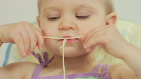 little finger : Charming little girl eating spaghetti with her fingers and enjoying it