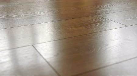 паркет : The camera moves along the floor, covered with laminated parquet with a brown wooden texture