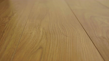 oak wood : The camera moves along the floor, covered with laminated parquet with a brown wooden texture