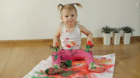 yelow : Little girl with smudgy paint fingers draws on a large sheet of white paper sitting on the floor Stock Footage