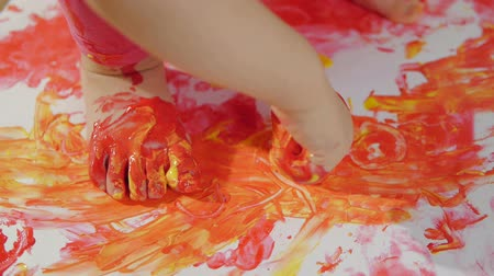 yelow : Closeup little girl with smudgy paint fingers draws on a large sheet of white paper sitting on the floor Stock Footage