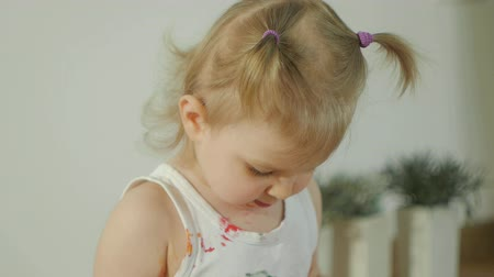 yelow : Closeup of a little girl, dirty in multicolored paints. The child learns to draw with finger paints Stock Footage