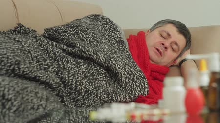 chřipka : A person with signs of a cold covered with a blanket lies in an apartment on the couch and blows his nose into a paper napkin