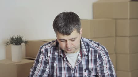 проведение : In an empty room, a man opens a cardboard box