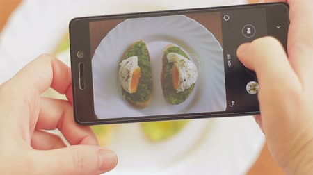 poached egg : A woman in a restaurant takes a picture of food with a mobile phone camera. Sandwich with poached egg and avocado Stock Footage