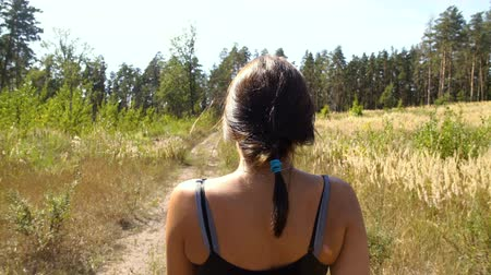 A girl walks along a forest trail, a sports caress, a back view