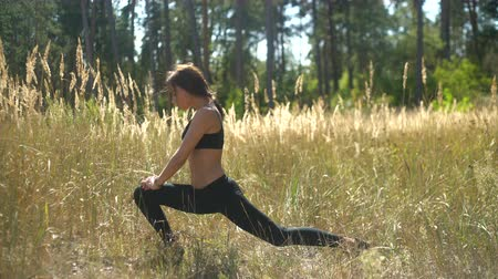 An attractive girl performs a sports exercise in the forest, a sexy sportswoman