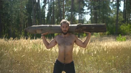 A sports guy performs strength exercises in nature, man pumps his muscles