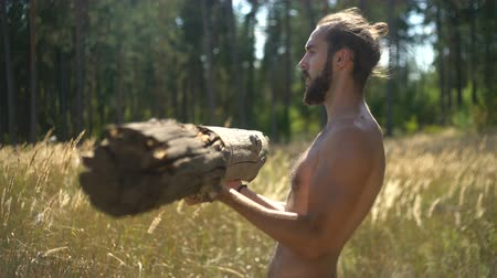 Bearded man swinging muscles, sport in nature, naked torso, sexy guy