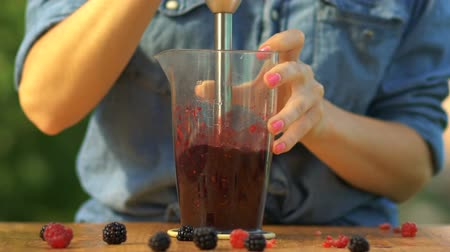 Preparation of smoothies from berries, a drink, a girl prepares smoothies