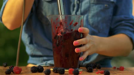 шейкер : The girl prepares smoothies from fresh berries, freshly squeezed juice