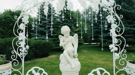 Statue of an angel boy on a pedestal, decorated with a playground for a holiday