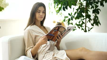 Young beautiful girl reading a magazine. Recreation. Output.