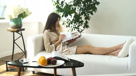 A girl in a cozy bright room reading a magazine on the couch