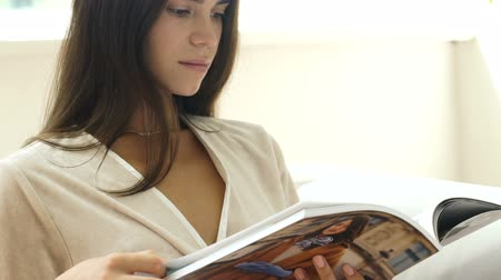 holding newspaper : Young beautiful girl reading a magazine. Recreation. Output.