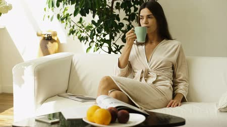 life energy : The girl with a glass in hands sits on a sofa and drinks a fresh juice Stock Footage