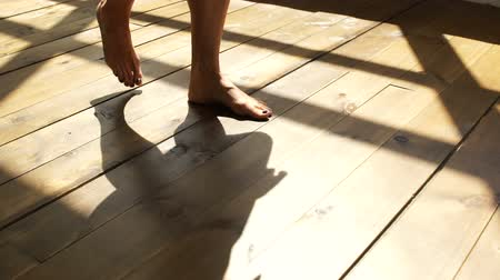 The girl is walking on the wooden floor. Female feet go on the wooden floor.