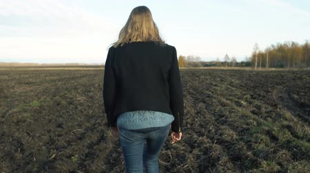A girl in a black coat walks the ground, autumn mood sadness