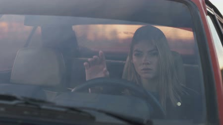 The girl stretches out her hand forward sitting in the car, Melancholy Stok Video