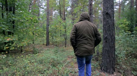 A guy in a hood walks through the forest, a man is lost in the woods