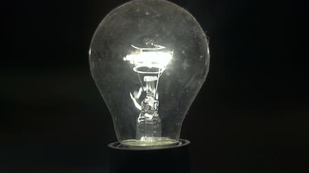 dazzle : The light bulb pulsates against a black background, the pulsation of incandescent light, the dimmer