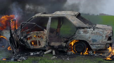 The car was set on fire in a green field, destroyed by a car