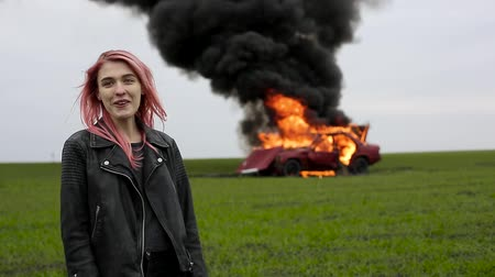 feminist : A girl sees a burning car and is surprised, surprise and smile, car on fire