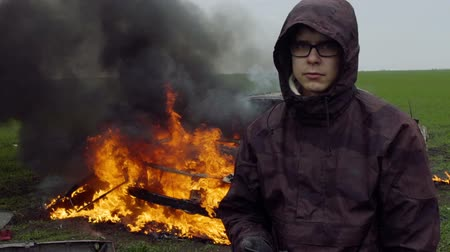 Portrait of a young man on the background of a burning car, car crash