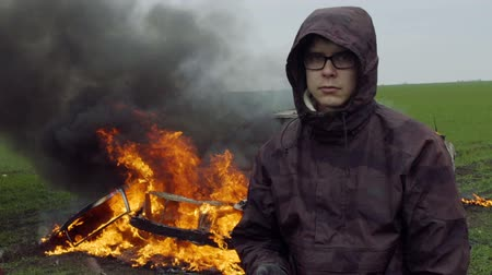 A guy stands on the background of a burning car, slow motion