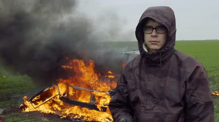 A guy in a hood and glasses stands on the background of a burning car, car explosion