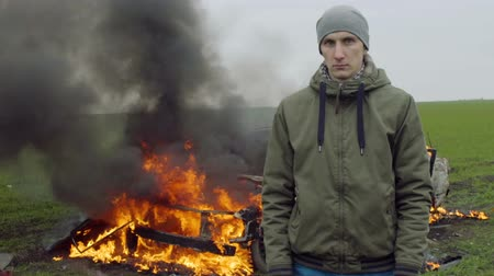 detonation : A stern young man in the background of a burning car, car explosion